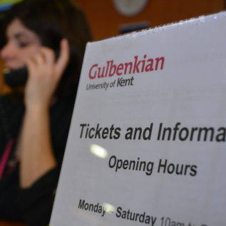 A poster showing Tickets and Information opening times and behind that a member of staff in uniform answering the phone.