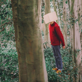 A man in a red sweater and blue jeans stands in the middle of a wood. He has a cardboard box on his head.