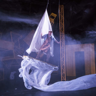 A man is suspended above the stage on a raft with billowing white sheets as sail and sea.
