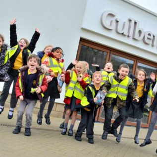 School children jump into the air in front of Gulbenkian