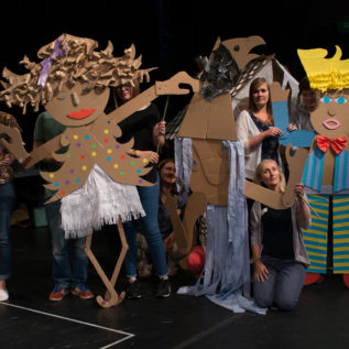 Teachers holding up cardboard characters they created during a CPD session at Gulbenkian