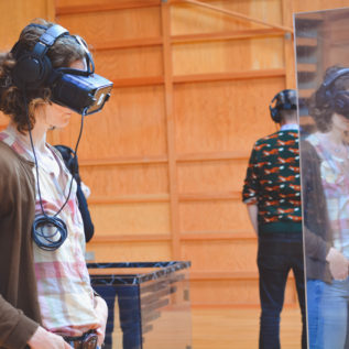 Audience member wearing a virtual reality headset is reflected in the object she is examining.