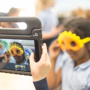 Boy holding an i-pad is filming a girl wearing a sunflower mask.