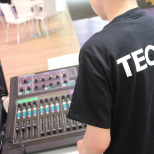 The back of a Tech 31 participant in tech 31 tshirt working on a sound desk