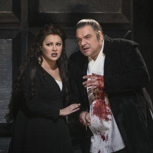Macbeth and Lady Macbeth talk. His shirt has blood on it.